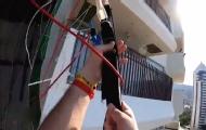 男子高空跳傘掛公寓外墻
